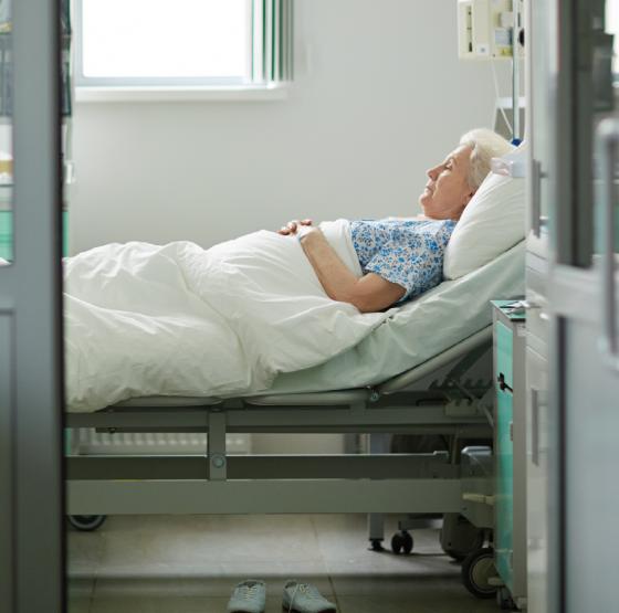 Frau liegt schwer krank im Krankenhaus